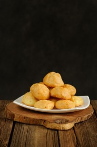 Gougeres on white plate on wooden background with space