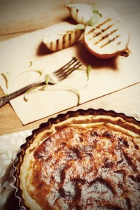 Onion Pie or Tart Served with Grilled Halves of Onion and Fresh Herbs. Rustic Style. Image Toned with Vintage Colors.